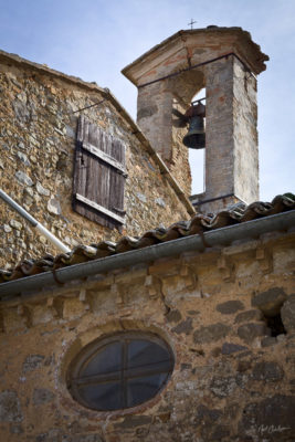 Montalcino, Italy - an old bell tower rises into the clear, blue, Tuscan sky.